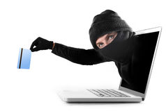 Cyber criminal out of computer grabbing and stealing credit card cyber crime concept. Anonymous hacker and cyber criminal man coming out from computer laptop royalty free stock photo