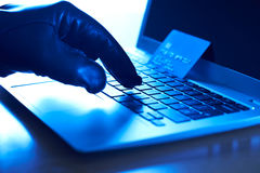 Cyber Criminal With Stolen Credit Card And Laptop Royalty Free Stock Image
