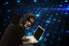 Cyber criminal wearing glasses is hacking from a laptop on matrix code rain background. Digital composite of hacker royalty free stock image