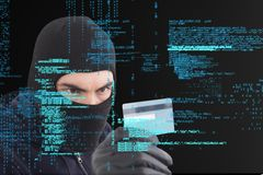 Cyber criminal wearing a hood is holding a credit card against matrix digital rain background Stock Photography