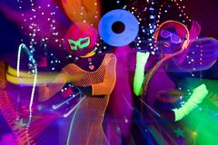 Glow uv neon disco party. 3 cyber glow raver friends filmed in fluorescent clothing under UV black light royalty free stock image