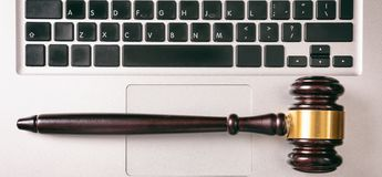 Gavel isolated on a computer keyboard background, top view. Cyber law or online auction concept. Judge gavel isolated on a computer keyboard top view Stock Photos