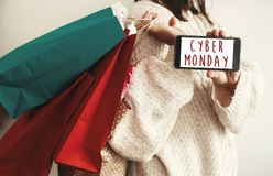 Cyber Monday text on phone screen. Special discount christmas of. Fer sign. Big Sales. Girl holding phone with Advertising message and carrying shopping bags royalty free stock photos