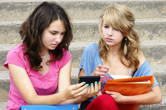 Cyber or online bullying concept. With two young women students or teenager girls shocked at the text they are reading on their cell phone, perfect for Royalty Free Stock Photography