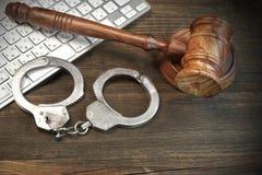 Cyber przestępstwa pojęcie, młoteczek klawiatura I kajdanki Na stole, Zdjęcia Stock