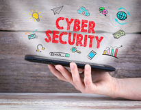 Cyber Security concept. Tablet computer in the hand. Old wooden background Stock Photos