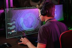 Cyber sport. Fully concentrated professional cybersport player playing important match. Professional photo of young male caucasian cyber sportsman in gaming club stock photography