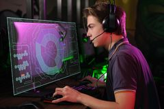 Cyber sport. Fully concentrated professional cybersport player playing important match. Professional photo of young male caucasian cyber sportsman in gaming club royalty free stock image