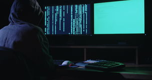 Cyber terror - computer hacker sitting in a dark room writing code. Cyber terror - computer hacker sitting in a dark room hacking computer systems