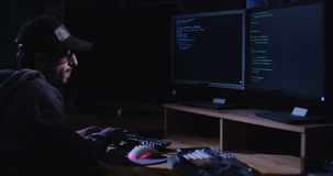 Cyber terror - computer hacker sitting in a dark room writing code stock footage