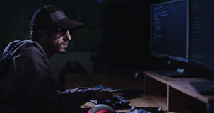 Cyber terror - computer hacker sitting in a dark room writing code stock video