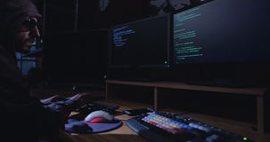 Cyber terror - computer hacker sitting in a dark room writing code stock video footage