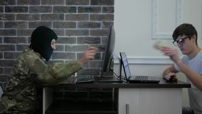 Cyber terrorism, terrorist in black mask pay bribe money to stock video