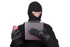 Cyber theft. Being committed through a tablet computer. Concept - A man in a balaclava is holding a tablet computer and credit card. White background royalty free stock photography