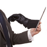 Cyber theft. Being committed through a tablet computer. Concept - A man in a suit is holding a tablet while a gloved hand is reaching through the screen to royalty free stock photos