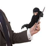 Cyber theft. Being committed through a tablet computer. Concept - A man in a suit is holding a tablet while a man in a balaclava is reaching through the screen royalty free stock photo