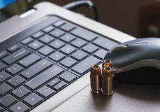 Cyber Warfare. Closeup of laptop computer, mouse, and gun bullets, representing the concept of cyber attacks stock photography