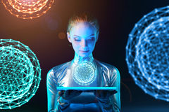 Cyber woman holding lighting panel with glowing polygonal abstract sphere. Futuristic cyber young woman in silver clothing holding lighting panel in her hands Royalty Free Stock Photo