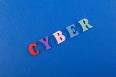 CYBER-Wort auf dem blauen Hintergrund verfasst von den hölzernen Buchstaben des bunten ABC-Alphabetblockes, Kopienraum für Anzeig Lizenzfreie Stockbilder