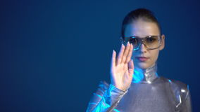 Cyber young woman in silver clothing turning over the virtual pages. Front view of serious cyber woman in silver clothing wearing eyeglasses turning over the stock footage