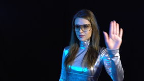 Cyber young woman in silver clothing turning over the virtual pages. Cyber young woman in silver clothing wearing eyeglasses turning over the virtual pages, over stock video