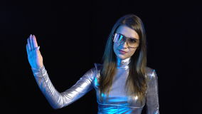 Cyber young woman in silver clothing turning over the virtual pages stock video
