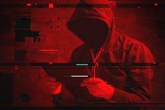 Cyberattack med den oigenkännliga med huva en hacker som använder minnestavlakomp