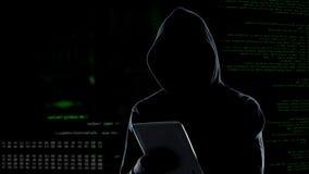 Cyberattack med den oigenk?nnliga med huva en hacker som anv?nder minnestavladatoren, cybercrime arkivbilder