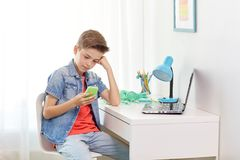 Boy with smartphone being bullied by text message. Cyberbullying, people and communication concept - boy with smartphone being bullied by text message at home Royalty Free Stock Images