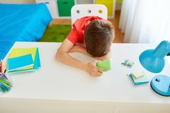 Tired or sad student boy with smartphone at home. Cyberbullying, technology and people concept - tired or sad student boy with smartphone lying on desk at home Royalty Free Stock Photos