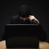 Cybercrime. As a hacker disguised in a balaclava sits in the darkness behind a laptop computer stealing personal or business information Royalty Free Stock Images