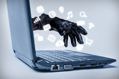 Cybercrime Concept. A gloved hand reaching out through a laptop with common media icons flowing, signifying a cybercrime or Internet theft while using various Stock Images