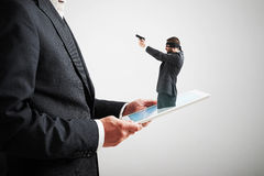 Cybercrime concept. Small man in mask and with gun got out of the tablet pc, and aiming at the big man over light grey background. cybercrime concept Royalty Free Stock Photos