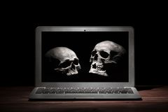 Cybercrime or hacking concept. Laptop in dark room under beam of light with skulls on a display. Idea of virus or worm program cyb. Er attack Royalty Free Stock Photos