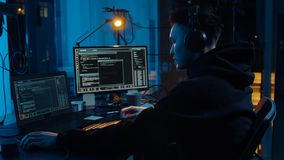 Hacker in headphones using laptop computer at night. Cybercrime, hacking and technology concept - asian male hacker in headphones with coding on laptop computer stock video footage