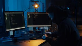 Hacker in mask using computers for cyber attack stock video