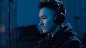 Hacker in headphones using computer at nigt stock video footage
