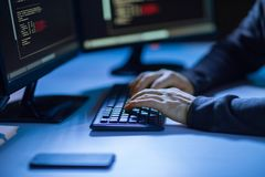 Hacker using computer virus for cyber attack. Cybercrime, hacking and technology concept - hands of hacker in dark room writing code or using computer virus stock image