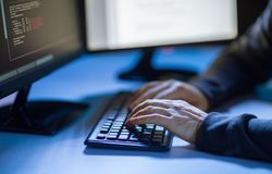 Hacker using computer virus for cyber attack. Cybercrime, hacking and technology concept - hands of hacker in dark room writing code or using computer virus Royalty Free Stock Photos