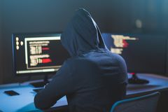 Hacker using computer virus for cyber attack. Cybercrime, hacking and technology concept - male hacker in dark room writing code or using computer virus program Royalty Free Stock Photos