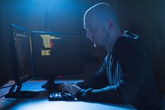 Hacker using computer virus for cyber attack. Cybercrime, hacking and technology concept - male hacker in dark room writing code or using computer virus program Royalty Free Stock Image