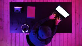 Cybercrime, hacking and technology concept - male hacker in dark room writing code or using computer virus program for stock image