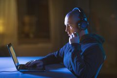 Hacker in headset typing on laptop in dark room Stock Images