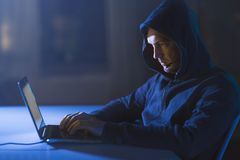 Hacker with microphone and laptop in dark room royalty free stock photo