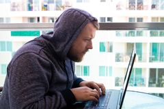 Cybercrime, hacking and technology concept - male hacker writing code or using computer virus program for cyber attack stock images