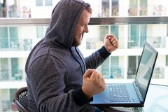 Cybercrime, hacking and technology concept - male hacker writing code or using computer virus program for cyber attack royalty free stock images
