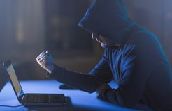 Hacker showing fist to laptop in dark room Royalty Free Stock Images