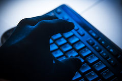 Cybercrime and internet security. Hand with black glove reaches out for black keyboard in blue light Royalty Free Stock Photo