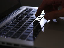 Cybercrime - one finger on lighted keyboard Royalty Free Stock Photography