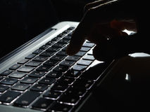 Cybercrime - one hand on lighted keyboard close up Stock Photo